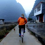 Ann riding bike in rain in China outback